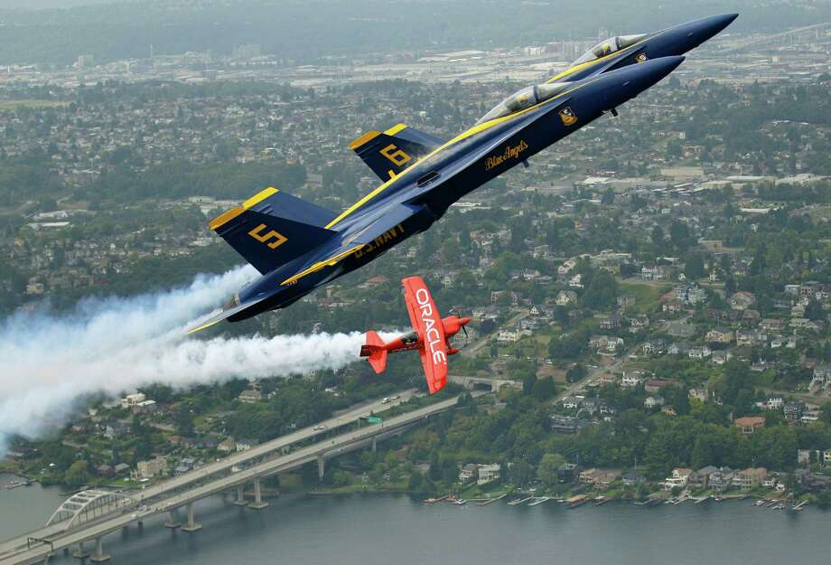 U.S. Navy Blue Angels pilots Lt. C.J. Simonsen (5) and Lt. David Tickle (6) fly in formation with Team Oracle stunt pilot Sean D. Tucker, Thursday, Aug. 2, 2012, over Lake Washington, in Seattle. Tucker and the Blue Angels are in town for the annual Seafair summer festival, which will feature an air show and other events this coming weekend. Photo: Ted S. Warren / Associated Press