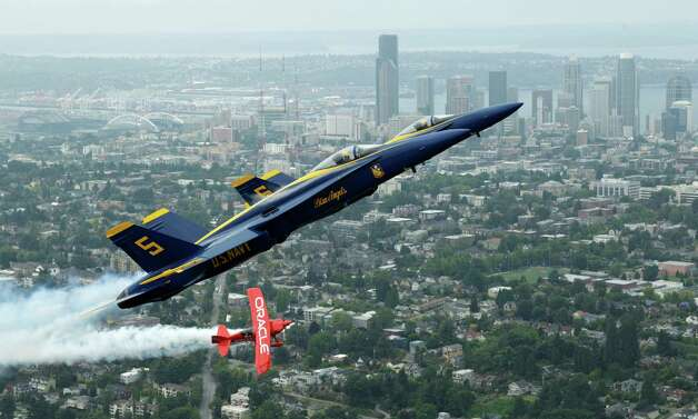 U.S. Navy Blue Angels pilots Lt. C.J. Simonsen (5) and Lt. David Tickle (6) fly in formation with Team Oracle stunt pilot Sean D. Tucker, Thursday, Aug. 2, 2012, near downtown Seattle. Photo: Ted S. Warren / Associated Press
