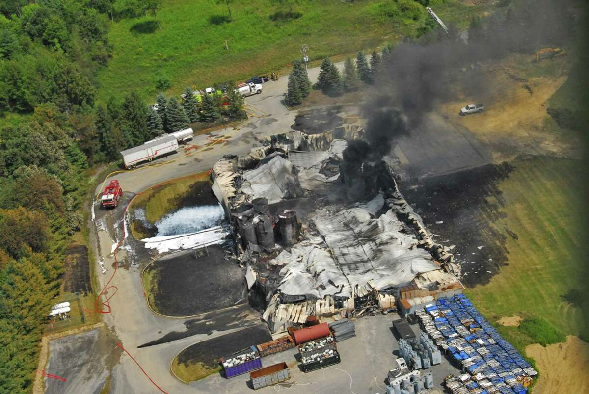TCI of New York, a transformer recycling company, smolders after it was destroyed by a large on Thursday, Aug. 2, 2012, in West Ghent, N.Y. The fire prompted warnings to residents of the largely rural area along the New York-Massachusetts state line to stay indoors for much of Thursday. Initial tests found no evidence of contamination. (AP Photo/Lance Wheeler)