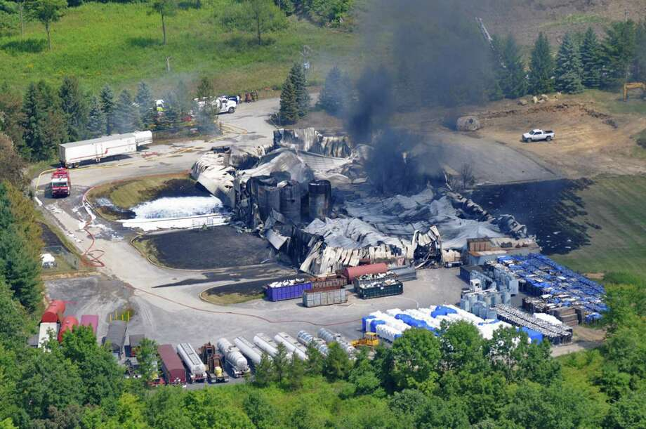 TCI of New York, a transformer recycling company, smolders after it was destroyed by a large on Thursday, Aug. 2, 2012, in West Ghent, N.Y. The fire prompted warnings to residents of the largely rural area along the New York-Massachusetts state line to stay indoors for much of Thursday. Initial tests found no evidence of contamination. (AP Photo/Lance Wheeler) Photo: Lance Wheeler