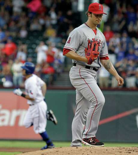 Angels starter C.J. Wilson grimaces after surrendering a solo home run to Rangers second baseman Ian Kinsler in the first inning of Texas' 15-9 win. Photo: LM Otero / AP
