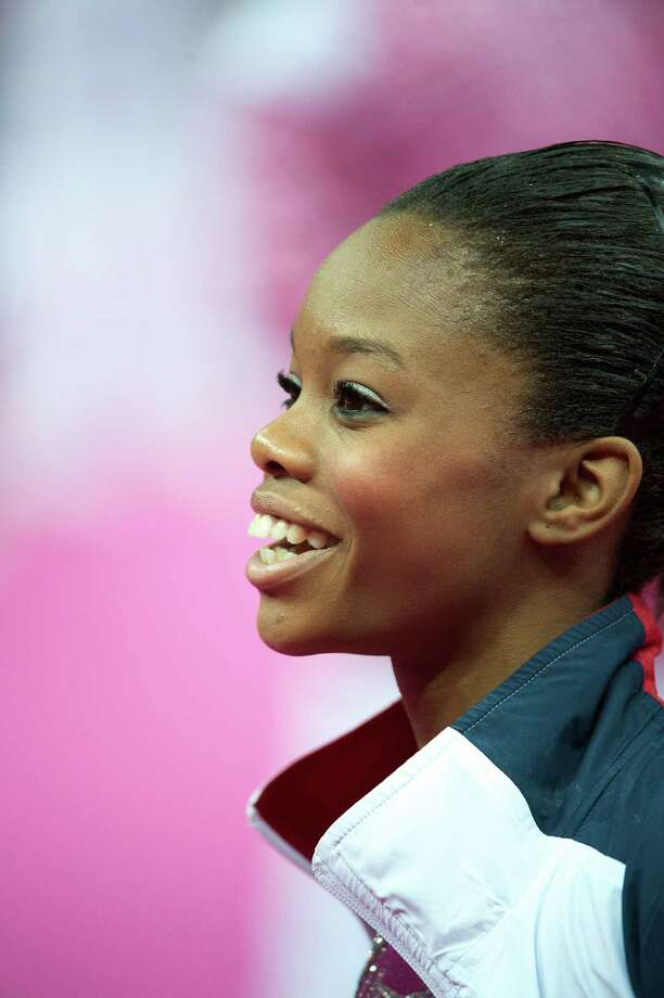 Even while waiting to perform during the all-around Thursday, U.S. gymnast Gabby Douglas flashes a golden smile. Photo: Smiley N. Pool / © 2012  Houston Chronicle