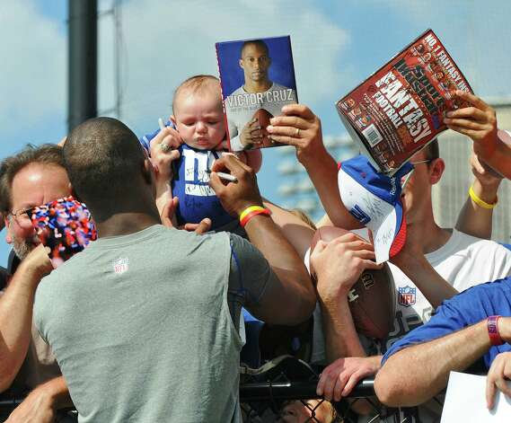 New York Giants wide receiver Victor Cruz signs autographs for fans after a training camp practice at UAlbany on Thursday Aug. 2, 2012 in Albany, NY.  (Philip Kamrass / Times Union) Photo: Philip Kamrass / 00018639A