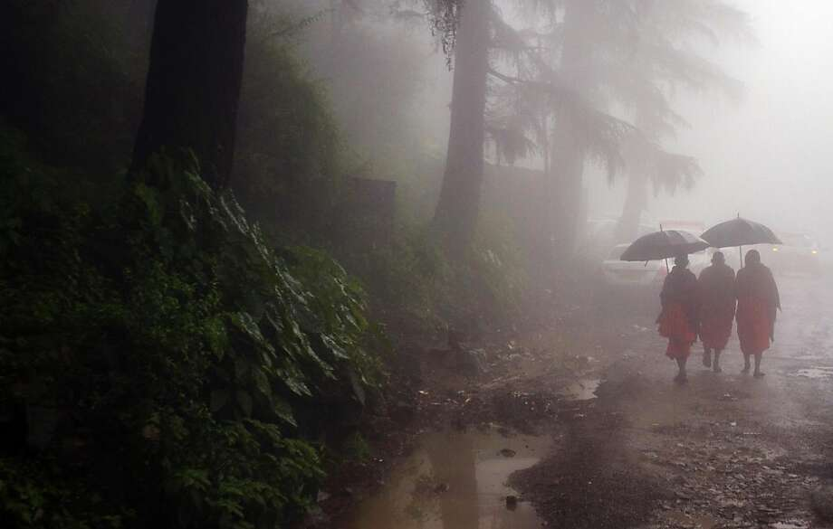 Buddhist monks walk in thick mist during a monsoonal rain in Dharmsala, India, Thursday, Aug. 2, 2012. The area receives heavy rainfall during the summer monsoon season though this year it has been lighter than usual. Photo: Ashwini Bhatia, Associated Press