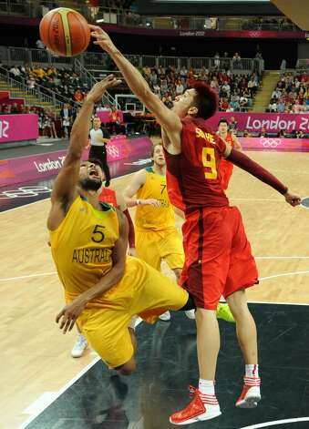 Australian guard Patrick Mills (L) vies with Chinese forward Sun Yue during the men's preliminary round Groupe B basketball match Australia vs China of the London 2012 Olympic Games  on August 2, 2012 at the basketball arena in London. Australia won 49-23. (MARK RALSTON / AFP/Getty Images)
