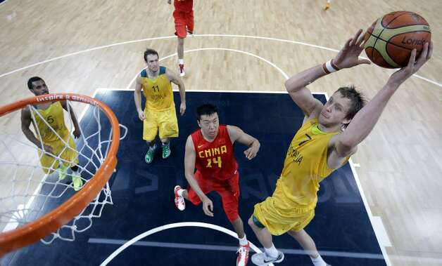 Australia's Joe Ingles (R) goes over China defender Wang Zhizhi during the men's preliminary round Groupe B basketball match Australia vs China of the London 2012 Olympic Games on August 2, 2012 at the basketball arena in London. Australia won 49-23. (ERIC GAY / AFP/Getty Images)