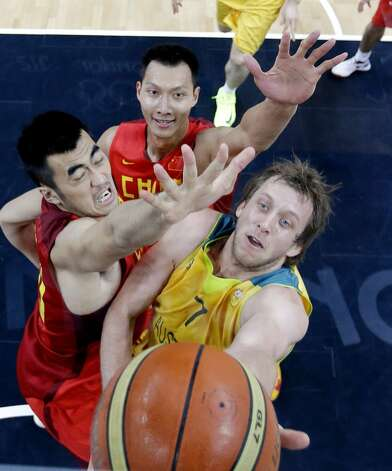 Australia's Joe Ingles (R) vies with China's Wang Zhizhi (L) and Yi Jianlian (top) as he tries to score during the men's preliminary round Groupe B basketball match Australia vs China of the London 2012 Olympic Games on August 2, 2012 at the basketball arena in London. Australia won 49-23. (ERIC GAY / AFP/Getty Images)