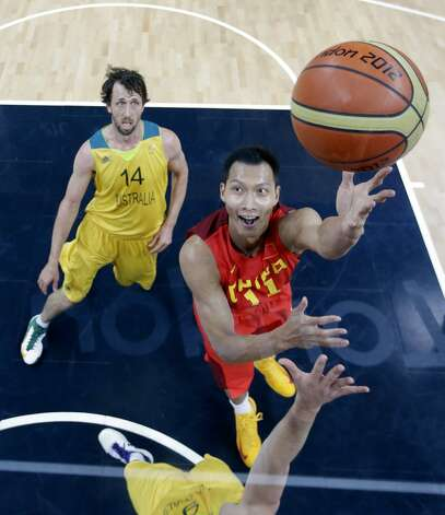 China's Yi Jianlian (R) shoots over Australia's Matt Dellavedova (bottom) and Matt Nielsen (L) during the men's preliminary round Groupe B basketball match Australia vs China of the London 2012 Olympic Games on August 2, 2012 at the basketball arena in London. Australia won 49-23. (ERIC GAY / AFP/Getty Images)