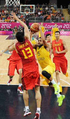 Australia's Patrick Mills drives against China's Chen Jianghua (13) during a men's basketball game at the 2012 Summer Olympics Thursday, Aug. 2, 2012, in London. (Mark Ralston / Associated Press)