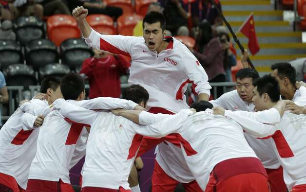 China's Zhang Zhaoxu leaps and pumps his fist as his team huddles prior to facing Australia during a men's basketball game at the 2012 Summer Olympics, Thursday, Aug. 2, 2012, in London. (Charles Krupa / Associated Press)