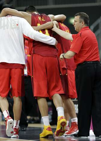 China's Yi Jianlian (11) is helped off the court after he injured his leg during a preliminary men's basketball game against Australia at the 2012 Summer Olympics, Thursday, Aug. 2, 2012, in London. (Eric Gay / Associated Press)