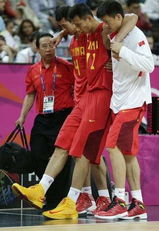 China's Yi Jianlian is helped off the court after an injury during a men's basketball game against Australia at the 2012 Summer Olympics, Thursday, Aug. 2, 2012, in London. (Charles Krupa / Associated Press)
