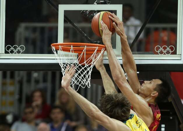 China's Yi Jianlian tries to tap a rebound against Australia's Matt Nielsen during a men's basketball game at the 2012 Summer Olympics, Thursday, Aug. 2, 2012, in London. (Charles Krupa / Associated Press)