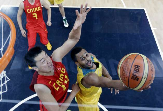 Australia's Patrick Mills, right, shoot around China's Wang Zhizhi, left, during a men's basketball game at the 2012 Summer Olympics, Thursday, Aug. 2, 2012, in London. (Eric Gay / Associated Press)