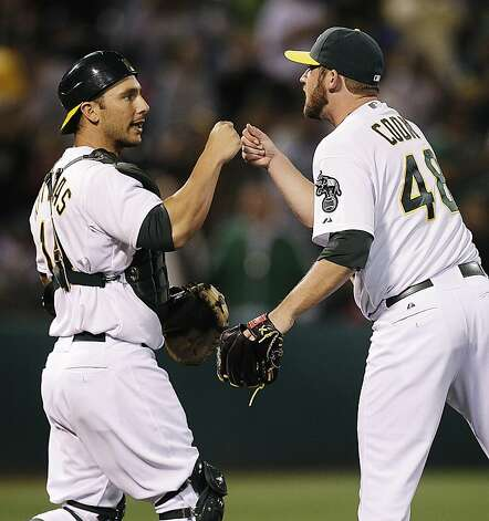 Oakland Athletics catcher George Kottaras, left, congratulates pitcher Ryan Cook at the end of a baseball game against the Toronto Blue Jays, Thursday, Aug. 2, 2012, in Oakland, Calif. The Athletics won 4-1. (AP Photo/Ben Margot) Photo: Ben Margot, Associated Press