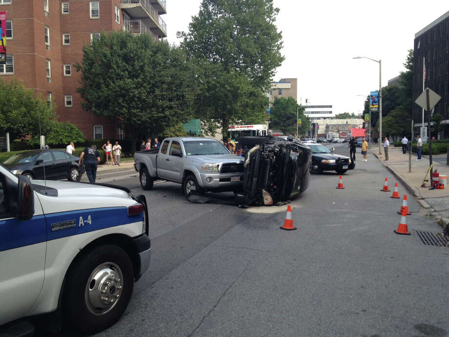 A car flipped over on Summer Street in downtown Stamford Friday morning backing up traffic throughout the area. Photo: John Nickerson