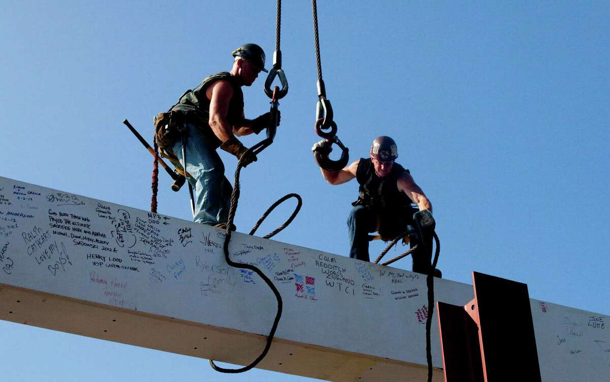 Ironworkers James Brady, left, and Billy Geoghan release the cables from a steel beam after connecting it on the 104th floor of 1 World Trade Center, Thursday, Aug. 2, 2012 in New York. The beam was signed by President Barack Obama with the notes: