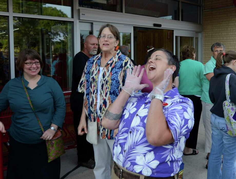 Crew member Shea Cusick fires up the patrons waiting to get in to the new Trader Joe's that opened this morning on Wolf Road in Colonie, N.Y. August 3, 2012.     (Skip Dickstein/Times Union) Photo: Skip Dickstein / 00018677A