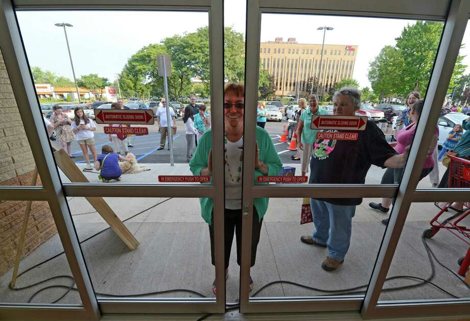 Barbara Hildreth sneaks a peek as she waits with a crowd of about 300 people to get in to the new Trader Joe's that opened this morning on Wolf Road in Colonie, N.Y. August 3, 2012.     (Skip Dickstein/Times Union) Photo: Skip Dickstein / 00018677A