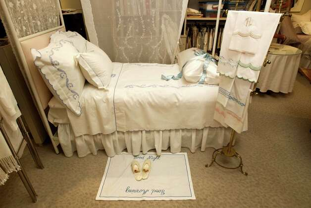 Custom embroidery on a bed, with a matching slipper mat, brings the design together. Photo: Brett Coomer, Houston Chronicle / © 2012 Houston Chronicle