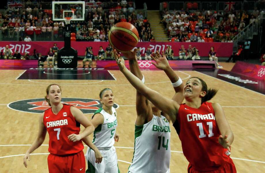 Canada's Natalie Achonwa (R) shoots past Brazil's Erika Souza (2ndR) as Canada's Courtnay Pilypaitis (L) and Brazil's Karla Costa (2ndL) look on during their women's preliminary round Group B basketball match at the Basketball Arena during the London 2012 Olympic Games August 3, 2012.           AFP PHOTO / MIKE SEGARMIKE SEGAR/AFP/GettyImages Photo: MIKE SEGAR, AFP/Getty Images / AFP