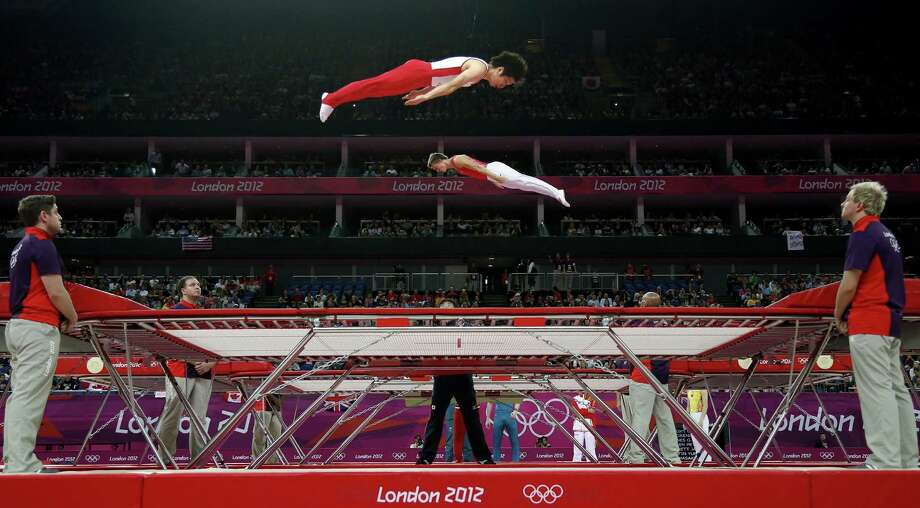 Gymnasts train before the men's trampoline final of the artistic gymnastics event of the London 2012 Olympic Games in London on August 3, 2012. China's Dong Dong won the gold, Russia's Dmitry Ushakov the silver and China's Lu Chunlong bronze. AFP PHOTO / THOMAS COEXTHOMAS COEX/AFP/GettyImages Photo: THOMAS COEX, AFP/Getty Images / AFP
