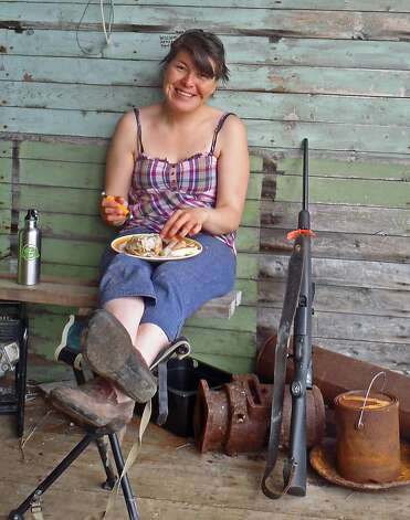 A park staffer enjoys a picnic lunch -- while keeping her bear rifle within reach. Photo: Bill Fink, Special To The Chronicle