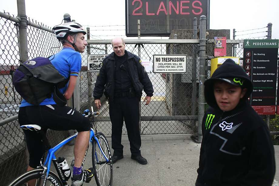 An officer with the Golden Gate Bridge Authority turns cyclists and walkers away from the bridge after a man climbed the South tower of the bridge a early Thursday evening closing foot traffic. He was apprehended in the morning of Friday Aug. 3, 2012 in San Francisco, Calif. Photo: Mike Kepka, The Chronicle