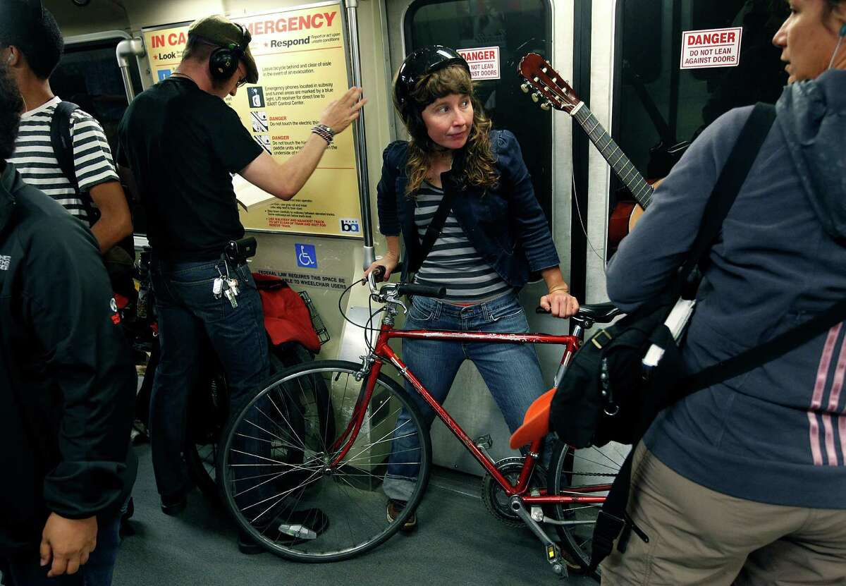 Kazoo Studio takes her two-wheeler on an inbound BART train from Oakland to San Francisco. The transit agency allows bicyclists to board during the rush hour with some limitations.