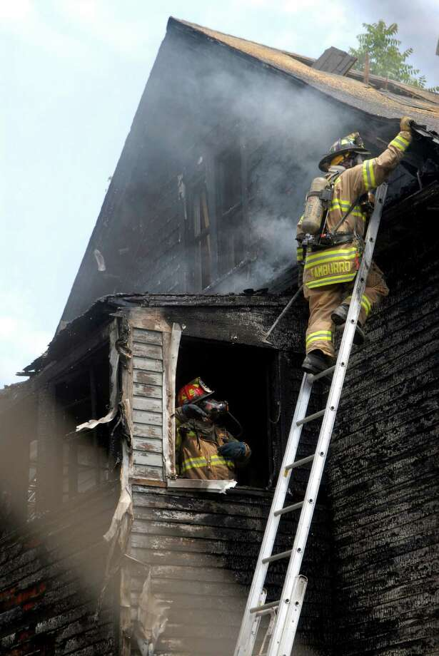 Firefighter pulls off roof tiles and siding at house fire at 303 Greenwich Ave in Stamford, Conn. on Friday August 3, 2012. Photo: Dru Nadler / Stamford Advocate Freelance