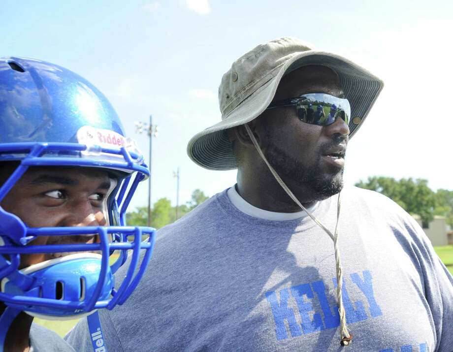 Kelly High School offensive line coach Frank Middleton, right, talks wtih running back Nick Barber, left, after practice on Thursday.  Middleton brings NFL experience to the Kelly Bulldogs football team from his playing years with the Oakland Raiders and Tampa Bay Buccaneers. Thursday, August 11, 2011 Valentino Mauricio/The Enterprise Photo: Valentino Mauricio