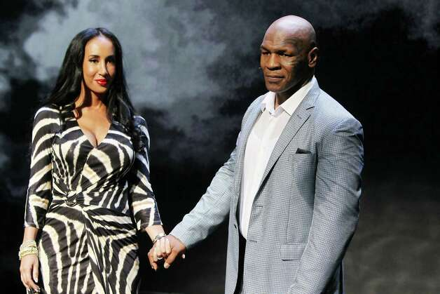"This image released by Starpix shows, former boxer Mike Tyson, right, holds hands with his wife Kiki Tyson at the curtain call for the opening night of ""Mike Tyson: Undisputed Truth,"" Thursday, Aug. 2, 2012 at the Longacre Theatre in New York.  The one man show starring Tyson was directed by Spike Lee, and written by Kiki Tyson. (AP Photo/Starpix, Amanda Schwab) Photo: Amanda Schwab"