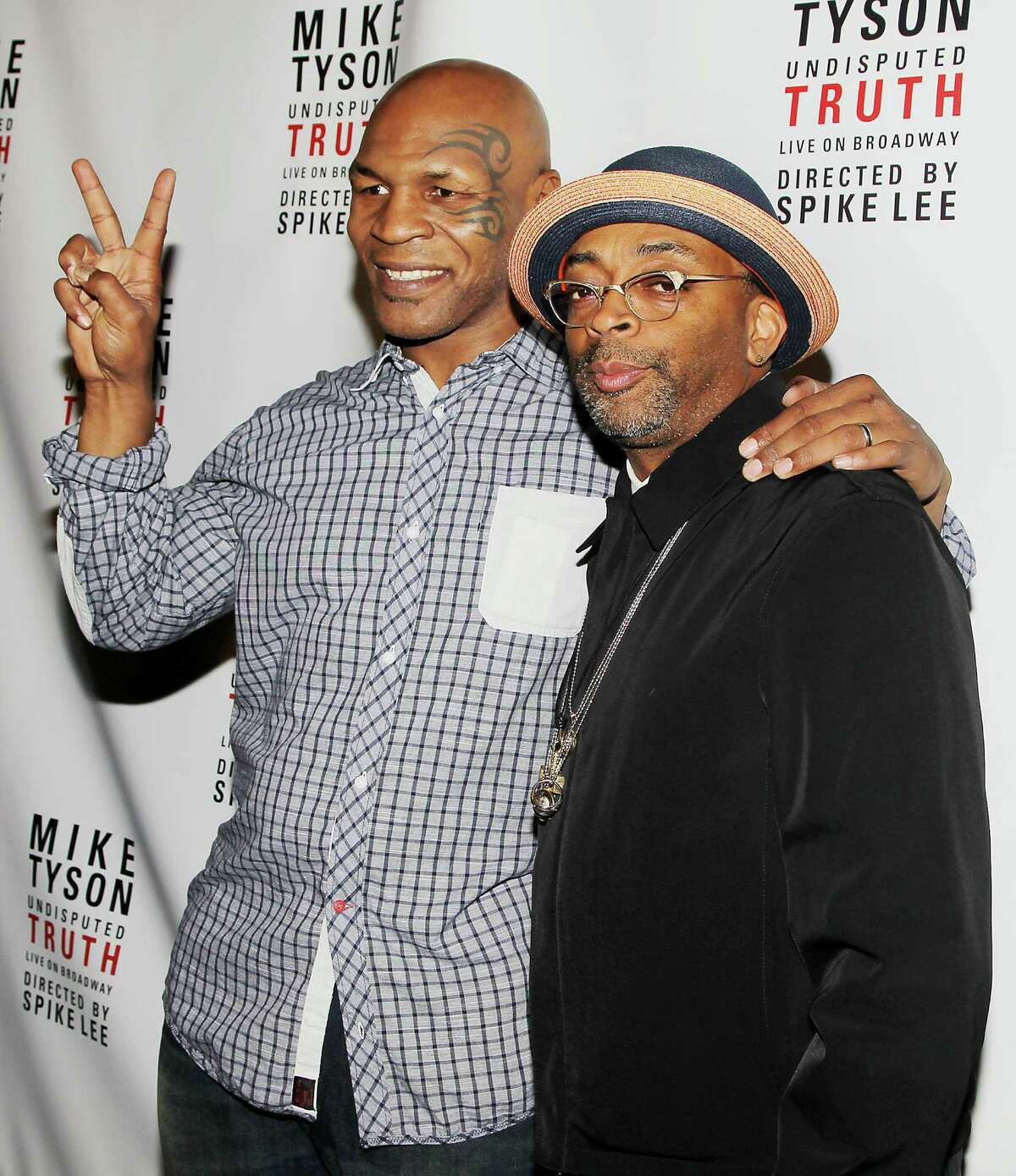 """This image released by Starpix shows, former boxer Mike Tyson, left, and Spike Lee pose backstage after the curtain call on the opening night of """"Mike Tyson: Undisputed Truth,"""" Thursday, Aug. 2, 2012 at the Longacre Theatre in New York. The one man show starring Tyson was directed by Spike Lee, and written by Tyson's wife Kiki. (AP Photo/Starpix, Amanda Schwab)"""