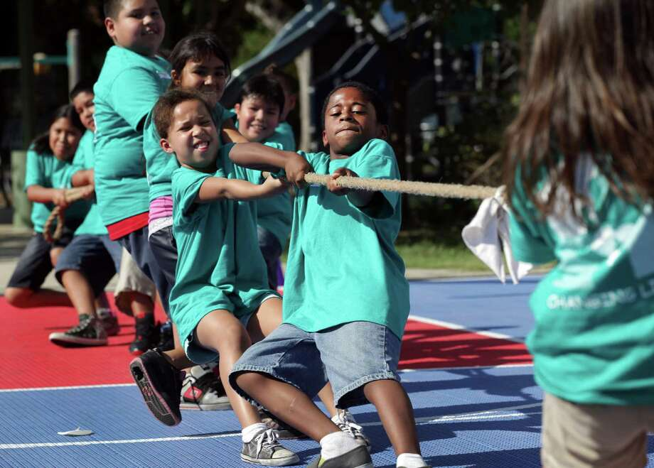 "Andre Walker, center, Allyza Dewitt, left, and others on thier team, struggle as they participate in a tug of war with other 8 and 9 yr olds at Camp ""Healthy Choices for Kids"", sponsored by the nursing department at UT Health Science Center, during the Kid's Olympics on the final day of the camp at Good Samaritan Community Services.  Friday, Aug. 3, 2012. Photo: BOB OWEN, San Antonio Express-News / © 2012 San Antonio Express-News"