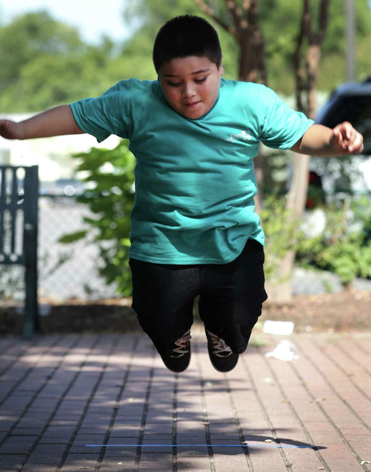 """Jose Ramon, 7 takes a try in the long jump at Camp """"Healthy Choices for Kids"""", sponsored by the nursing department at UT Health Science Center, during Kid's Olympics on the final day of the camp at Good Samaritan Community Services. Friday, Aug. 3, 2012."""