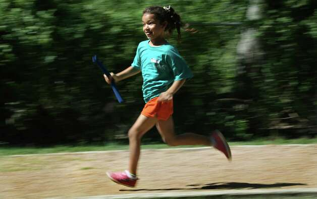 "Deana Martinez hold the baton as she competes in a relay race at Camp ""Healthy Choices for Kids"", sponsored by the nursing department at UT Health Science Center, during Kid's Olympics on the final day of the camp at Good Samaritan Community Services.  Friday, Aug. 3, 2012. Photo: BOB OWEN, San Antonio Express-News / © 2012 San Antonio Express-News"