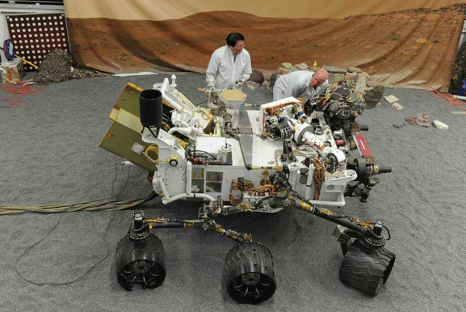 Jet Propulsion Laboratory (JPL) engineers James Wong (L) and Errin Dalshaug (R) examine a full size engineered model of the Mars rover Curiosity at JPL in Pasadena, California August 2, 2012. NASA said Thursday all was well ahead of its nail-biting mission to Mars, with its most advanced robotic rover poised to hunt for clues about past life and water on Earth's nearest planetary neighbor. On a two-year journey to seek out signs of environments that once sustained life, the landing of the Mars Science Laboratory and the largest and most sophisticated rover ever built, Curiosity, is set for 1:31 am August 6 (0531 GMT).  AFP PHOTO / ROBYN BECKROBYN BECK/AFP/GettyImages Photo: ROBYN BECK, AFP/Getty Images / AFP