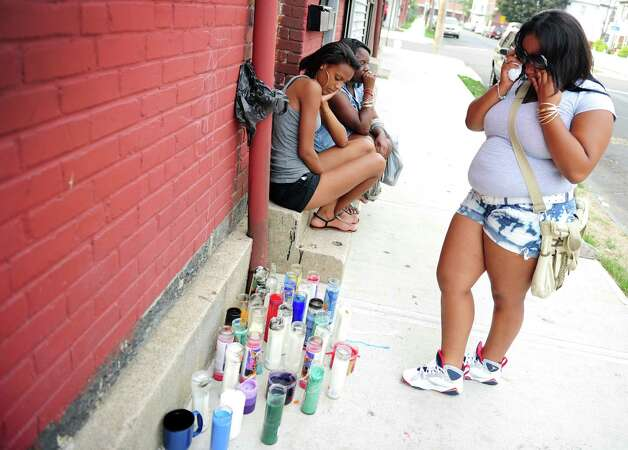 Seventeen-year-old Veronica Shanks wipes away tears as she looks at a memorial set up for friend Gary Gullap Friday, August 3, 2012 on Hallett Street in Bridgeport where 17-year-old Gullap was killed in a drive by shooting on Thursday afternoon. Photo: Autumn Driscoll / Connecticut Post