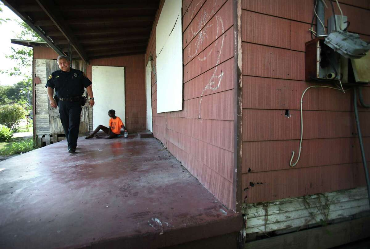 San Antonio Police Officer Carlos Solis, a veteran of 22 years, walks away after checking on a homeless woman, down and out on the front porch of an abandoned house in the 600 block of Leal St., across from Haven for Hope. Thursday, Aug. 2, 2012.