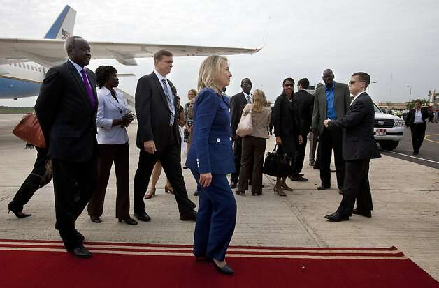 US Secretary of State Hillary  Clinton(C) and South Sudan's Foreign Minister Nhial Deng Nhial, far left, walk to a vehicle as the Secretary arrives for her first visit to South Sudan at Juba International Airport in Juba, South Sudan, on  August 3, 2012.AFP PHOTO/POOL/Jacquelyn Martin Photo: Jacquelyn Martin, AFP/Getty Images