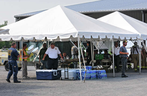 Emergency workers get food and water under tents at the command station off Falls Industrial Road that leads to the scene where a fire erupted late Wednesday night at the TCI of New York  Friday, Aug. 3, 2012 in Ghent, N.Y. Police still have the road closed off to the public and media. (Lori Van Buren / Times Union) Photo: Lori Van Buren