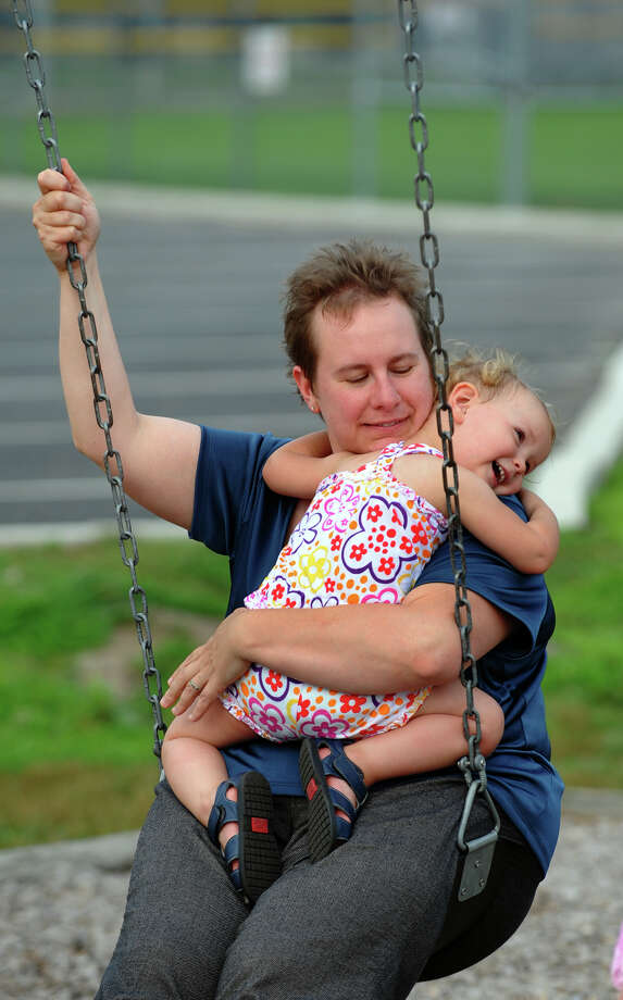 Karen Widdows, of Milford, holds her adopted daughter Angelina Hart, 2, as they ride on the swingset in the playground behind the Milford Public Library in downtown Milford, Conn. on Friday August 3, 2012. Photo: Christian Abraham / Connecticut Post