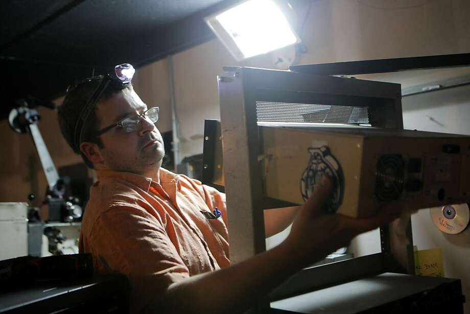 Joel Miller of Northwest Projection & Sound in Portland, Ore., removes the 35mm projector from the Marina Theatre to install a digital version. Photo: Megan Farmer, The Chronicle