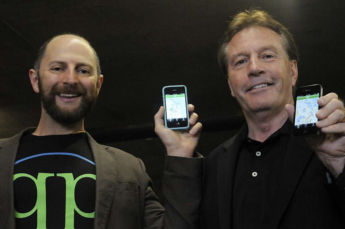 QuickPay Chairman Barney Pell, left, and Founder Carl Muirbrook, pose for a photo showing their phone application that lets parking lots lease out spaces at times when they are not being used by regular parkers. The application also allows customers to pay using their credit cards by scanning a QR code.