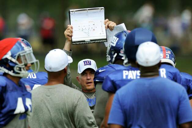 Peter Giunta, New York Giants secondary coach of cornerbacks holds up the play sheets during Giants Camp on Friday, Aug. 3, 2012, at the UAlbany in Albany, N.Y. (Cindy Schultz / Times Union) Photo: Cindy Schultz / 00018640A