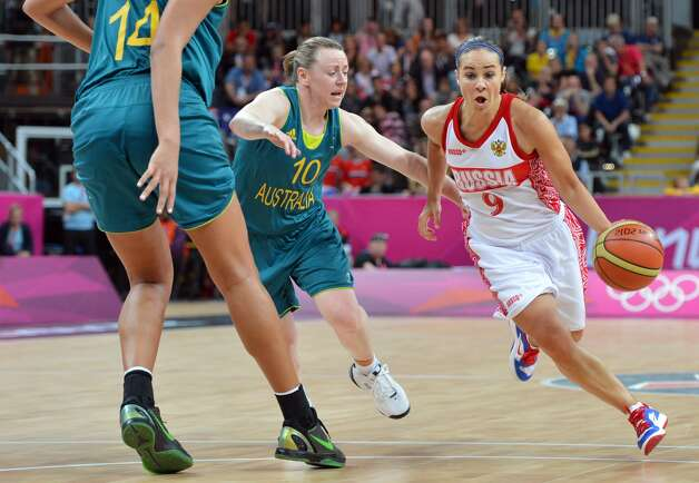 Russian guard Becky Hammon (R) runs past Australian guard Kristi Harrower (C) during the women's preliminary round group A basketball match of the London 2012 Olympic Games Russia vs. Australia on August 3, 2012 at the basketball arena in London. Australia won 70 to 66.  AFP PHOTO MARK RALSTONMARK RALSTON/AFP/GettyImages (MARK RALSTON / AFP/Getty Images)