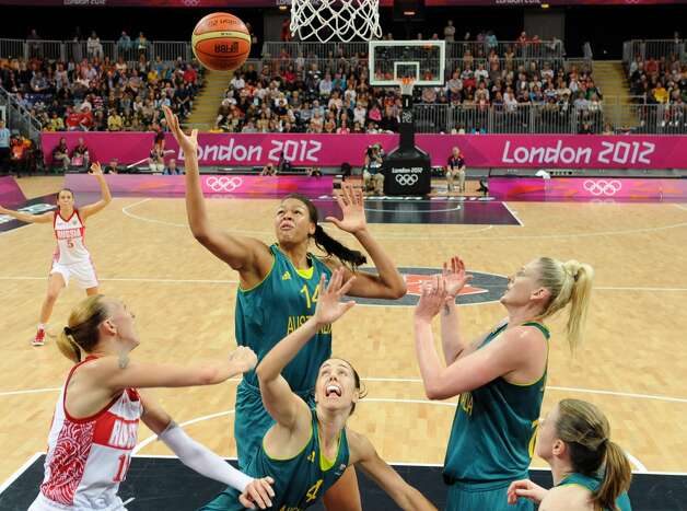 Australia's Elizabeth Cambage, center, vies for possession with Russia's Irina Osipova, left, during their preliminary women's basketball game at the 2012 Summer Olympics, Friday, Aug. 3, 2012, in London. (AP Photo/Mark Ralston, Pool) (Mark Ralston / Associated Press)