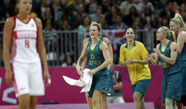 Australia's Jennifer Screen (6) celebrates with teammates as Russia's Alena Danilochkina (8) walks off the court during their preliminary women's basketball game at the 2012 Summer Olympics, Friday, Aug. 3, 2012, in London. (AP Photo/Eric Gay) (Eric Gay / Associated Press)