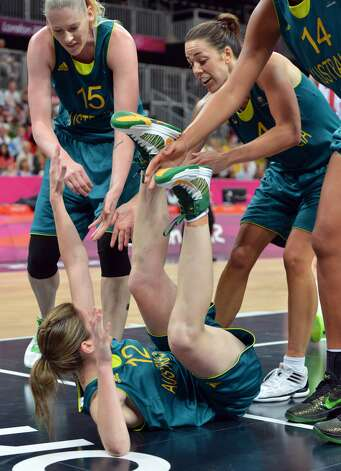 Australian guard Belinda Snell (down) is helped by teammates after falling down during the women's preliminary round group A basketball match of the London 2012 Olympic Games Russia vs. Australia on August 3, 2012 at the basketball arena in London. Australia won 70 to 66.  AFP PHOTO MARK RALSTONMARK RALSTON/AFP/GettyImages (AFP/Getty Images)