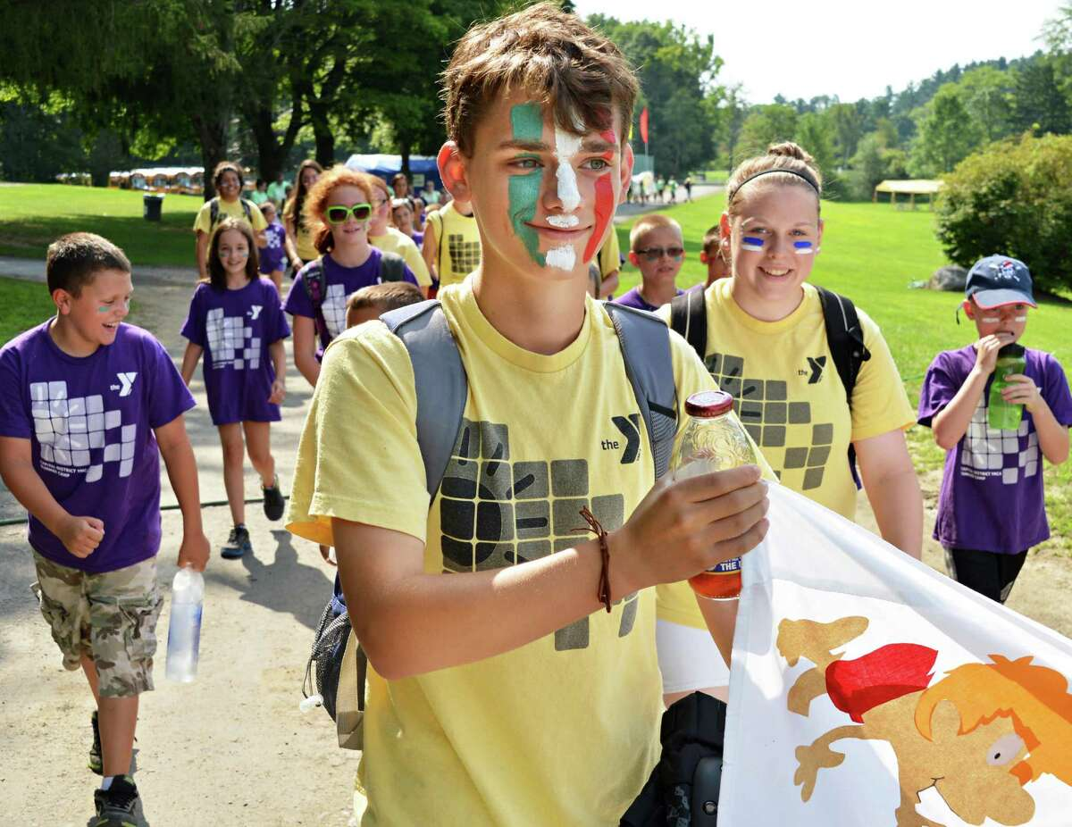 Tom Russo, 15, helps carry the Greenbush Y's banner in the opening parade as 1500 children from 8 YMCA branches in the region participate at the Capital District YMCA's 2012 Ultimate Summer Games at YMCA Camp Nassau in Guilderland Friday, Aug. 3, 2011. (John Carl D'Annibale / Times Union)